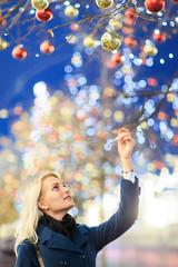 Image of beautiful woman touching Christmas balls on tree