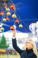 Picture of beautiful woman touching Christmas balls on tree