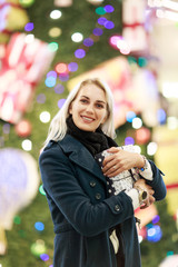 Image of smiling woman in coat with gift box on background of Christmas tree in store.