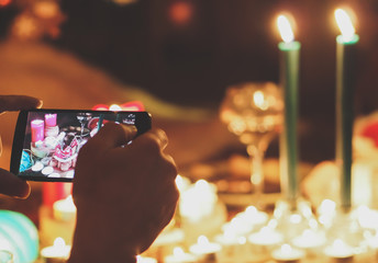 Human hand holding mobile phone and taking picture of New Year accessories, candles and food on the table. Film effect filter.