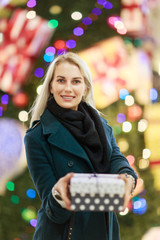 Portrait of beautiful girl in coat with gift box on background of Christmas tree