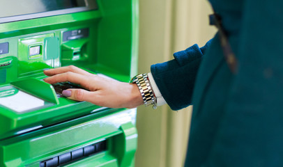 Image of woman in coat at green cash machine