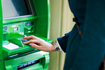 Image of girl picking pincode at green cash dispenser