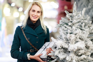 Image of woman with gift in box of white Christmas tree in store.