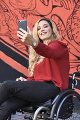 Bella ragazza in carrozzina si fa selfie