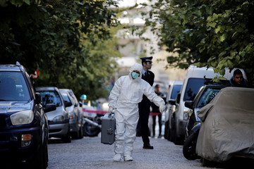 A forensics officer carries equipment following an operation in which Greek security services raided Athens apartments and found bomb-making equipment, in Athens
