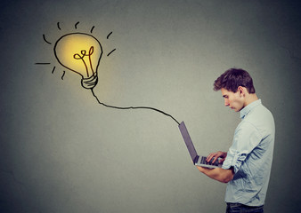 Young man using a laptop with light bulb plugged in it