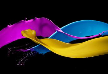Getti di pittura colorata si scontrano, spruzzando su fondo nero