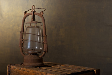 Old Rusty Lantern on the Wooden Desk in the Attic