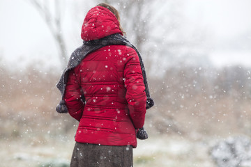 woman in red coat walking in heavy snowfall in the countryside