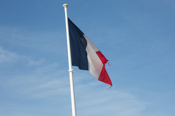 A white and red blue French flag flutters in the sky