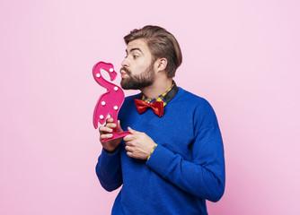 Playful man kissing artificial a  flamingo .