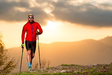 Man athlete practicing trail with sticks at sunset Wall mural