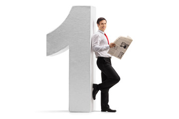 Formally dressed man with a newspaper leaning against a cardboard number one