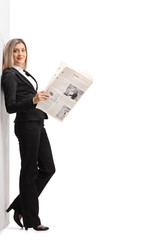 Formally dressed woman with a newspaper leaning against a wall