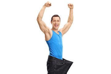 Overjoyed muscular guy wearing a pair of oversized jeans