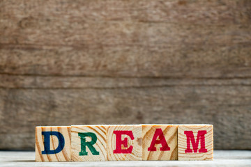Letter block in word dream on wood background