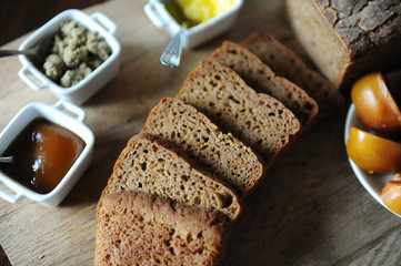 Fresh homemade unleavened bread on the leaven is sliced on a wooden board. Serving of breakfast