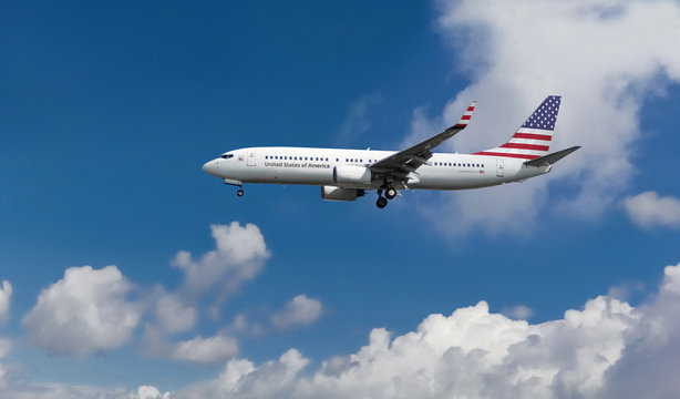 Commercial airplane with American flag on the tail and fuselage landing or taking off from the airport with blue cloudy sky in the background