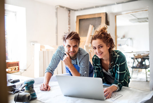 Young couple with laptop in the carpenter workroom.