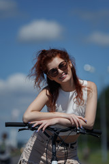 Beautiful young girl in sunglasses enjoying the warm summer weather, resting on the wheel of bicycle.