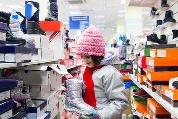 girl choosing shoes in   children's store for   winter.