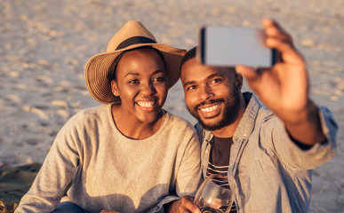 Happy young African couple taking selfies together at the beach