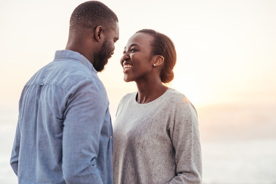 Smiling young African couple talking together at the beach
