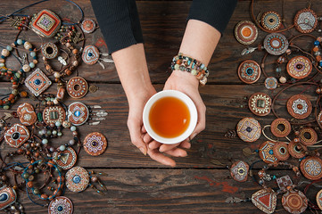 Hands with a tea bowl on a wooden table with clay ethnic decorations. View from above
