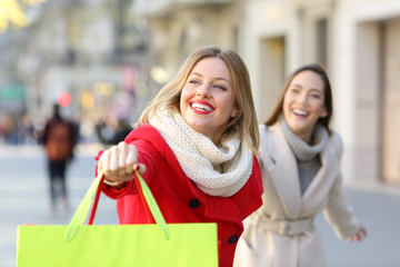 Two happy shoppers running on the street