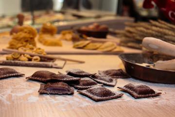 Black Ravioli Italian Pasta on Wooden Board with Flour