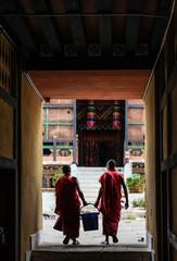 Punakha, Bhutan - September 11, 2016: Two Bhutanese monks carrying a bucket in Chimi Lhakhang (Monastery of Fertility), Bhutan
