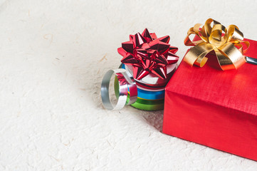 Christmas gift set for packing. Colorful ribbon and bow on textured background with empty space for your design