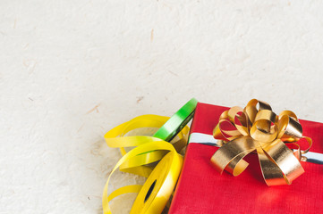Christmas concept. Red present box with gold bow and yellow ribbon stripes with Empty space for your logo or design
