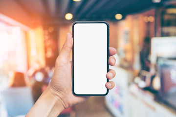 Man's hand shows mobile smartphone with white screen in vertical position, Blurred or Defocus image of Coffee Shop or Cafeteria for use as Background vintage tone. - mockup template and clipping path