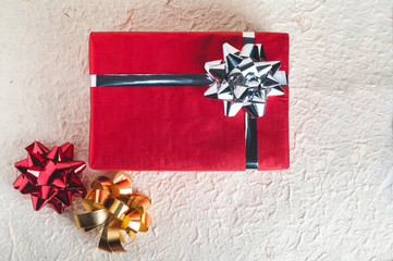Top view on red present with silver ribbon and bow on textured paper background