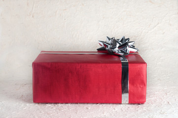 One red gift box or present with silver ribbon and bow on textured paper surface for Christmas design