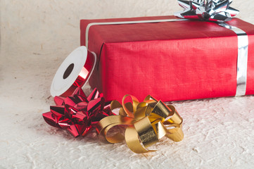 Red present box with silver bow and ribbon stripe behind heap of bow for Christmas design