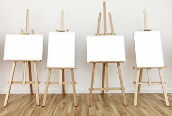 Four art studio easels with blank white frames to add paintings or pictures