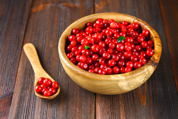Cowberry, foxberry, cranberry, lingonberry in a wooden bowl on a brown wooden table.
