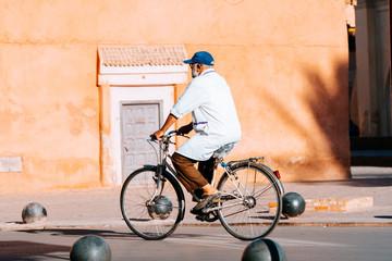 old man riding a bike inside marrakech medina, morocco
