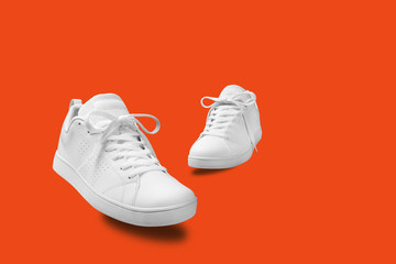 Pair of White sneaker isolated on orange background with clipping path Wall mural
