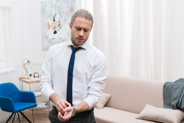 Handsome businessman putting on watch at home