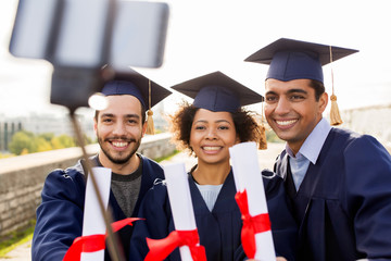 students or graduates with diplomas taking selfie
