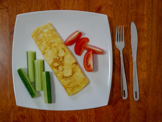 Classic omelet with tomatoes and cucumbers on the white plate. Fresh breakfast.