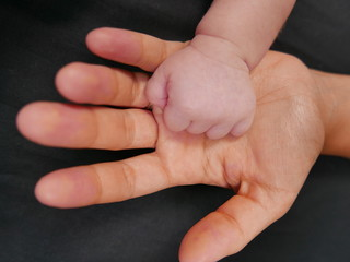 motherhand and babyhand isolated on a black background