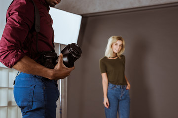 selective focus of african american photographer with photo camera and beautiful model in studio