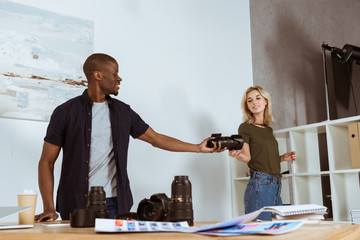 smiling caucasian photographer giving photo camera to african american colleague at workplace in studio
