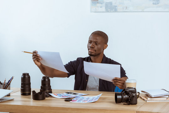 portrait of focused african american photographer looking at photoshoot examples at workplace