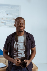 portrait of african american photographer with photo camera leaning on workplace in office